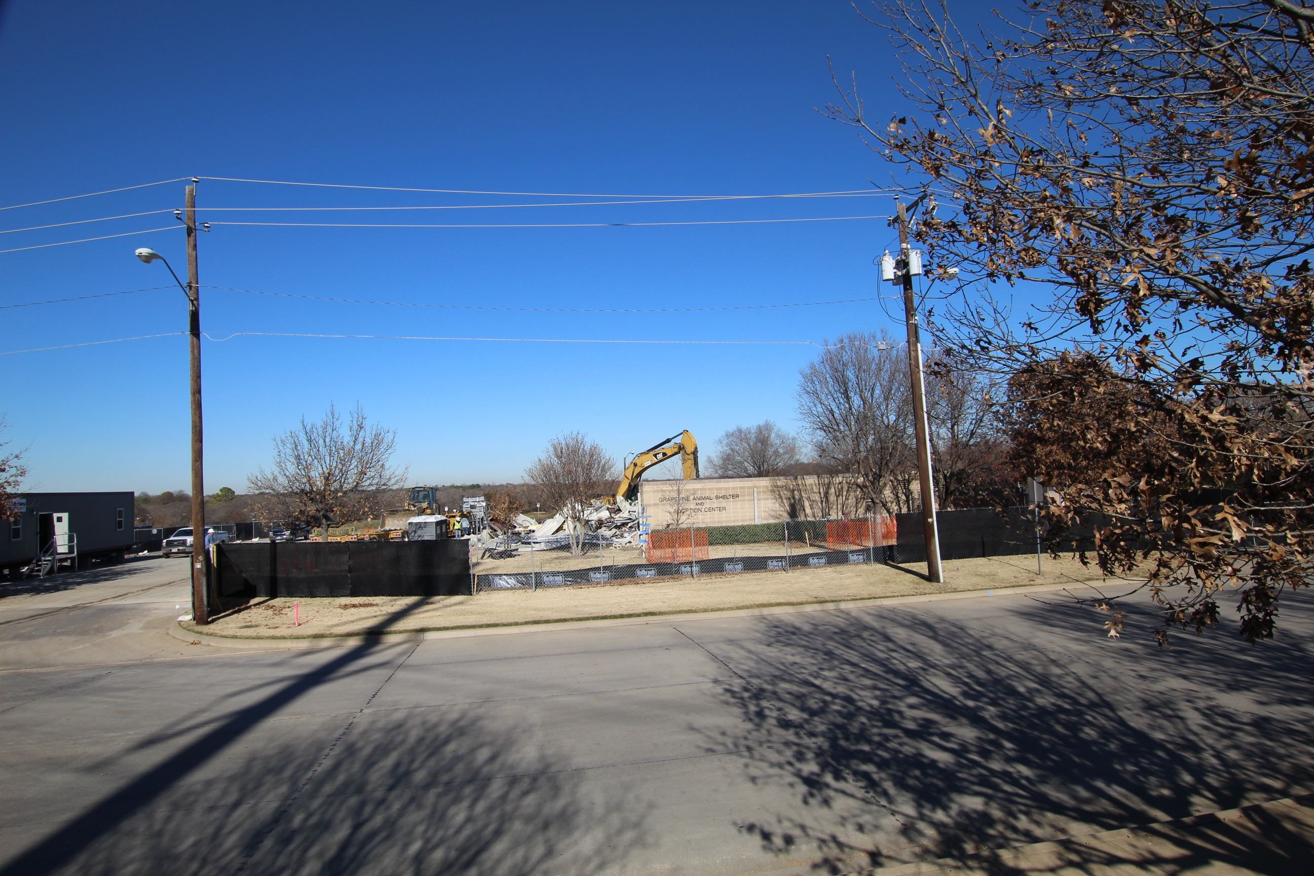 Gray building being demolished by equipment