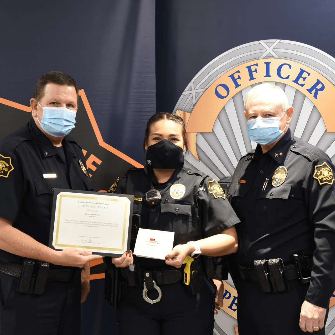 Three police officers in masks holding an award