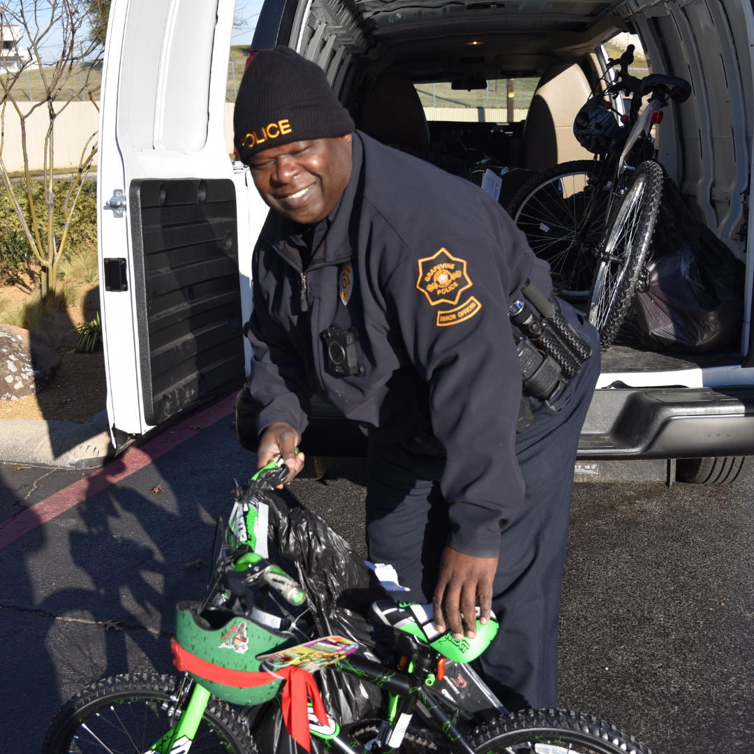 Smiling Grapevine Police officer unloading a Christmas bicycle from patrol vehicle