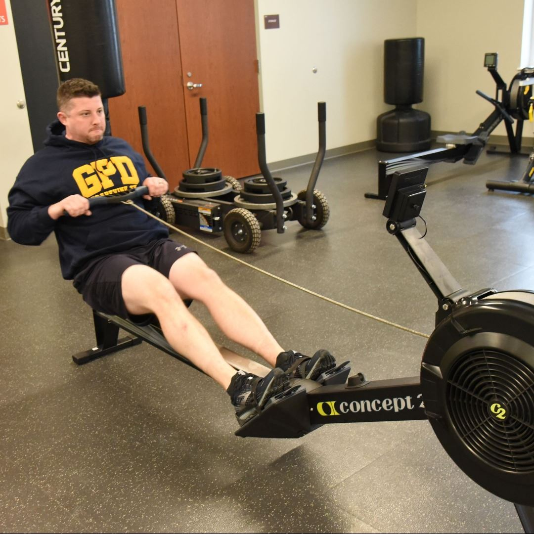 Man in gym using rowing machine